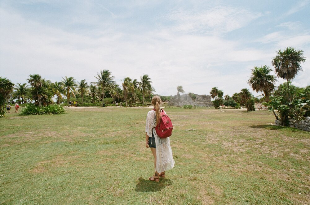 Taylor stands among ruins and palm trees at the Tulum ruins while wearing a red backpack