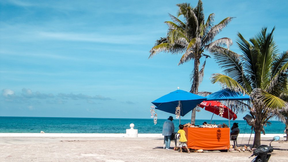 A mother and son attend to their seashell stand with palm trees in front of the ocean in Isla Mujeres, Mexico