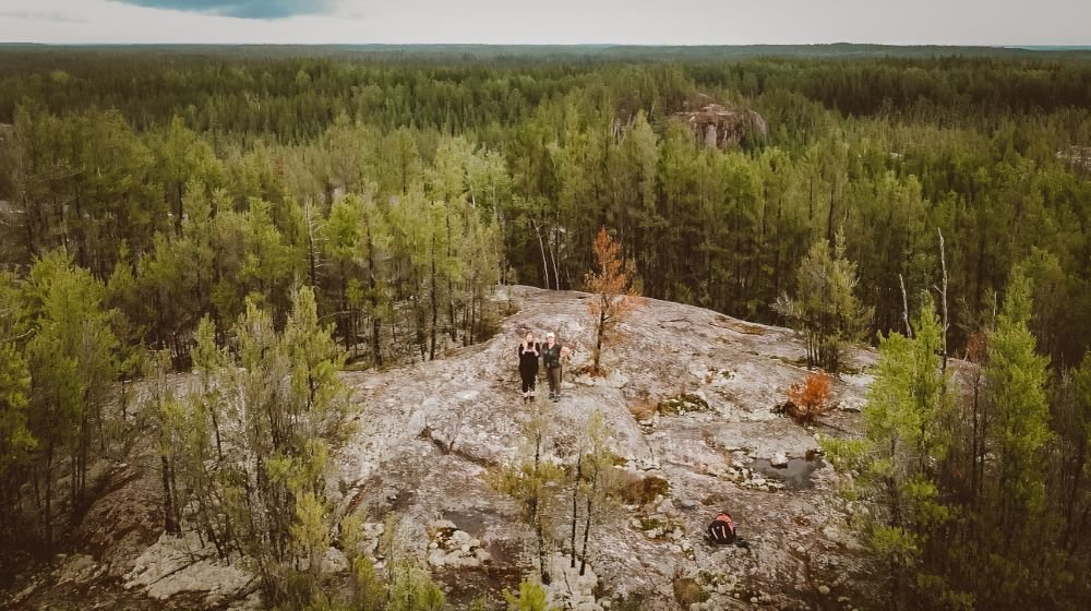 An aerial shot of two women standing on a large rock in the middle of a boreal forest in Manitoba, Canada