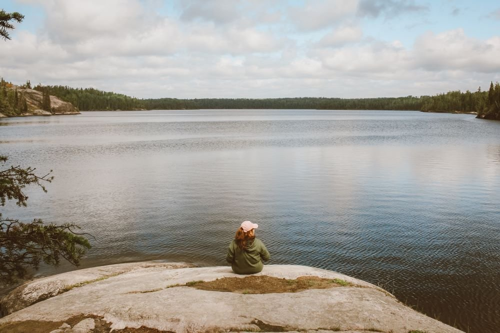 Rita sits with her back to the camera looking out over Tulabi Lake in Nopiming Provincial Park, Manitoba