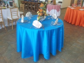 A round table fully equipped with cloth, napkins and dishware