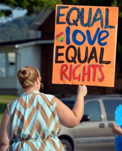 Maria Blevins of Morehead, Ky., waves her sign at passing cars during a protest on the lawn of the Rowan County Courthouse in Morehead, Ky., Saturday, Aug. 29, 2015. The rally, held by the Rowan County Rightas Coalition, brought roughly a hundred people to celebrate same sex marriage. (AP Photo/Timothy D. Easley)