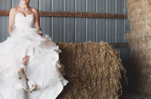 Bride in White Dress Sitting on Bales of Straw in a Barn