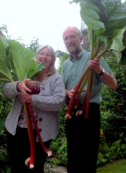 A couple holding large rhubarb bunches