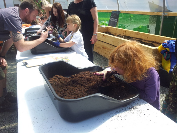 Children filling pots with potting mix in polytunnel