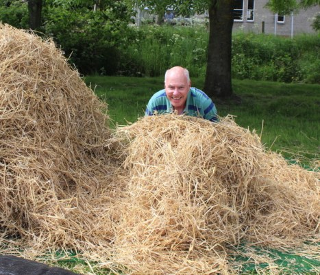 A man behind a stack of hay