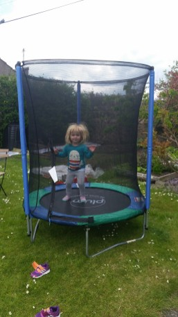 A photo of a girl jumping on the trampoline
