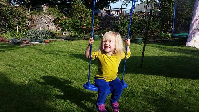 a photo of a girl on a garden swing