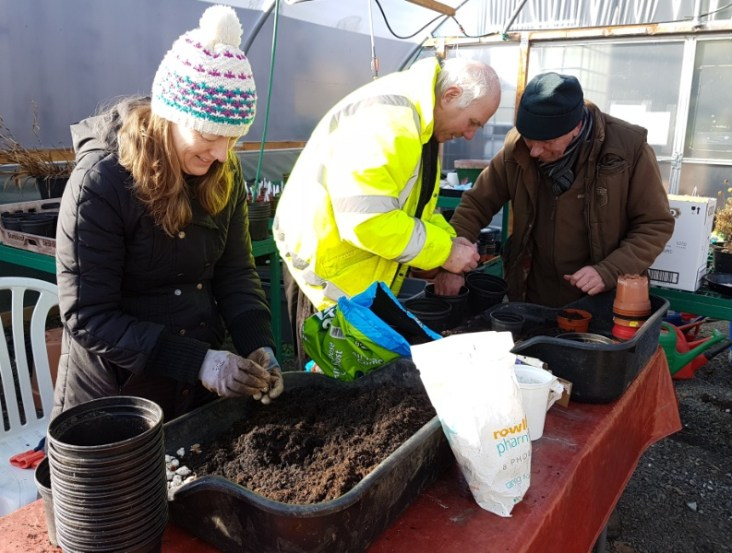A photo of Ian, Shona and Peter planting bulbs for Shona's wedding at the Garden