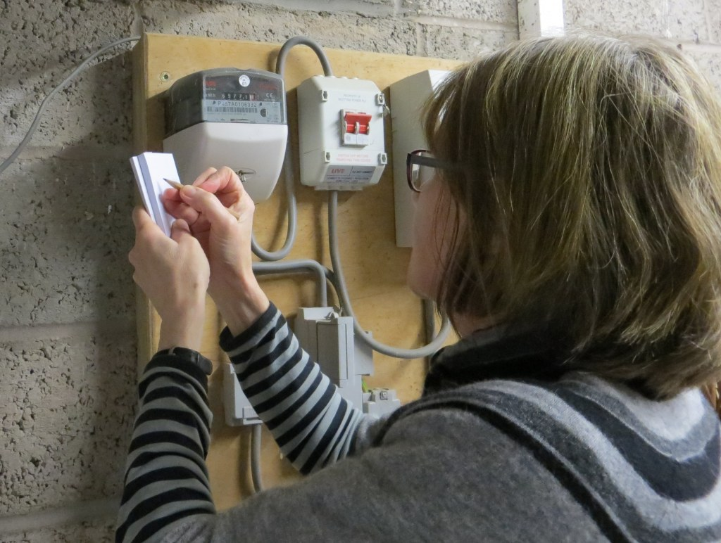 A photo of Kathleen checking energy meters