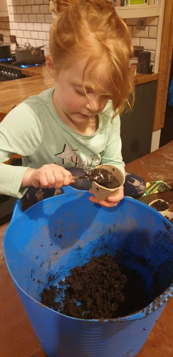 Photo of child filling a pot with composyt