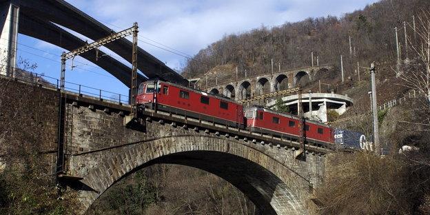 ein roter Zug überquert eine alte Brücke