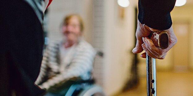 Zwei alte Menschen mit Krückstock und Rollstuhl