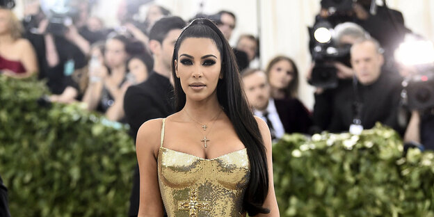 Kim Kardashian is posing in a gold glittering dress