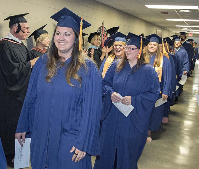 Line of students in blue caps and gowns walking down hallway to ceremony