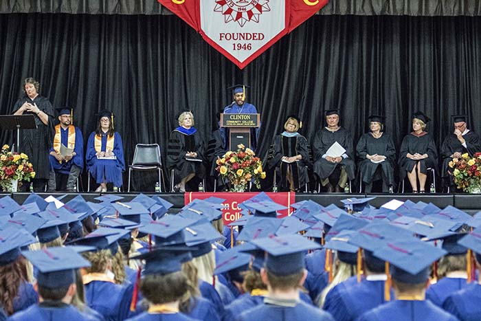 Student standing on stage at podium giving commencement speech