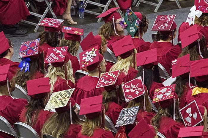 Nursing graduates with decorated graduation caps sitting in rows during commencement ceremony