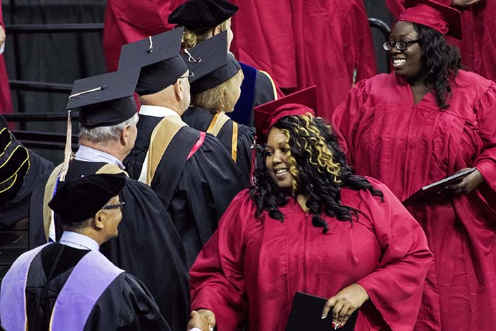 Graduate walking across stage shaking hands after receiving their degree
