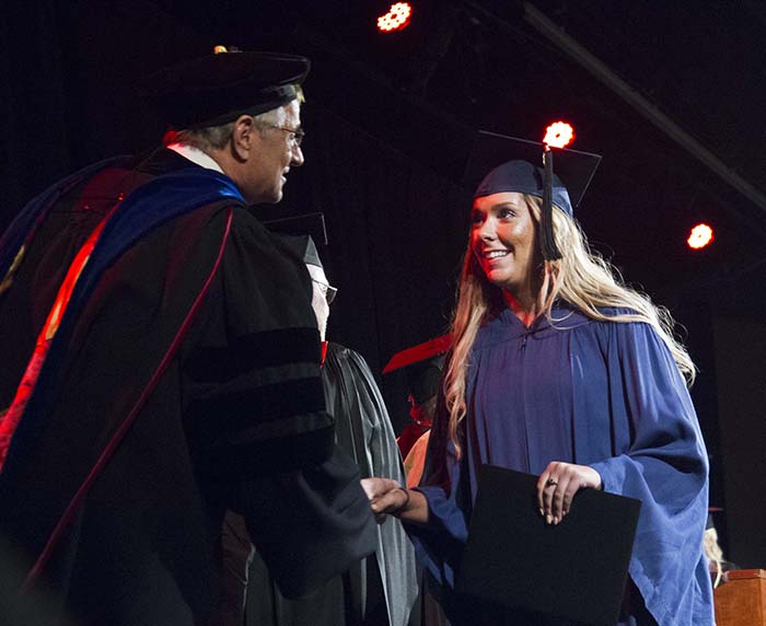 Female student shaking Chancellor Doucette's hand after accepting her degree