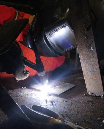 Student wearing welding mask welding