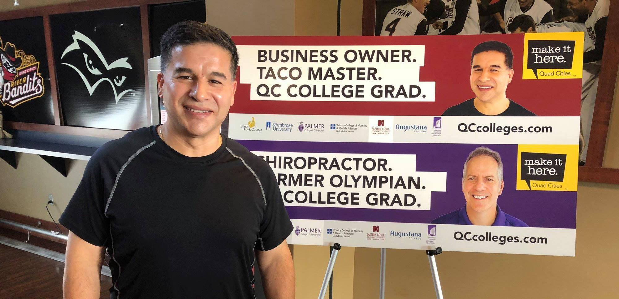 Joe Gomez standing with QC Colleges Billboard designs