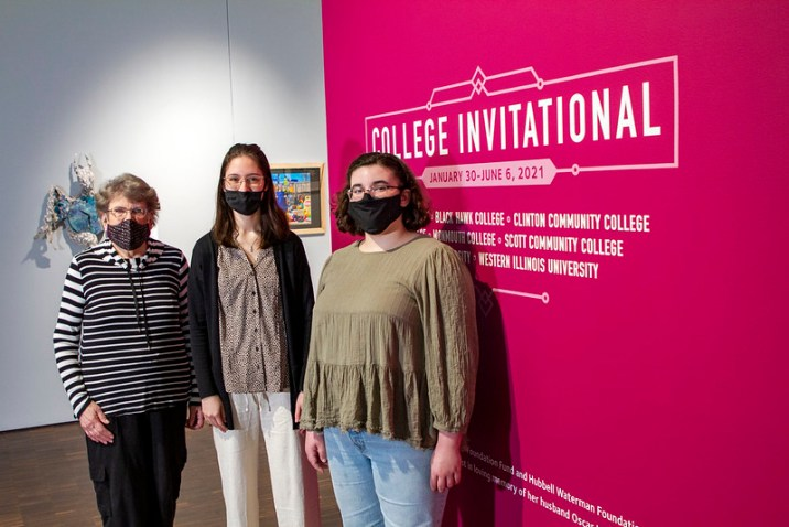 Artists standing in front of Figge Invitation Signage