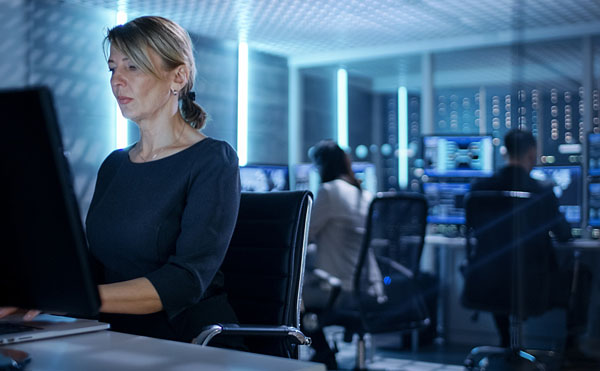 Female Hacker Works on Her Desktop Computer in a Cybercriminal Hacker Ring. Her Team is Plotting the Top 8 Cybersecurity Threats of 2020. In the Background People at Their Workstations with Multiple Screens Showing Graphics.