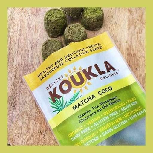 Photo of an open package of Koukla Delights Matcha Tea Macaroons, with the treats spilling out onto a table.