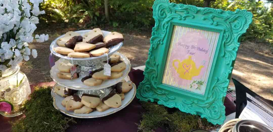 """A photo of a tiered treat stand holding cookies shaped like teabags next to a frame with a cutout of a teapot and the words """"Happy Birthday Jae!"""""""