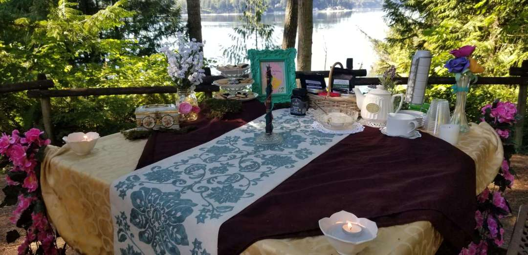 A photo of a table decorated with different fabrics, with teapots and a tiered tray of cookies.