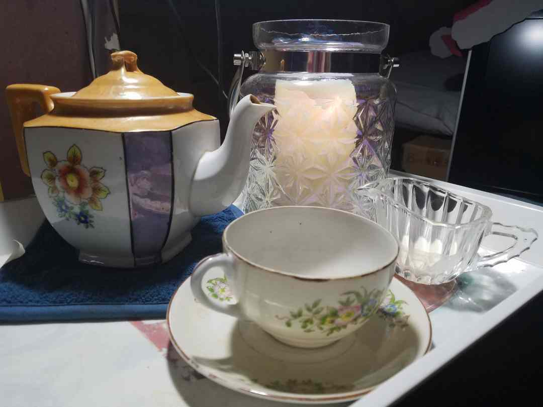 Solstice Night, Tea, and Light - Photo of a candle in a glass jar, teapot, tea cup, and creamer dish