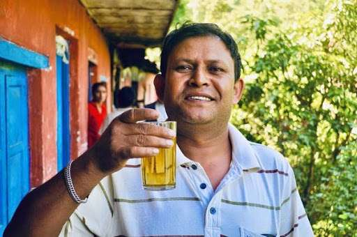 A Day In the Life at Nepal Tea's Family Farm - Photo of Dhan Bahadur with a glass of tea