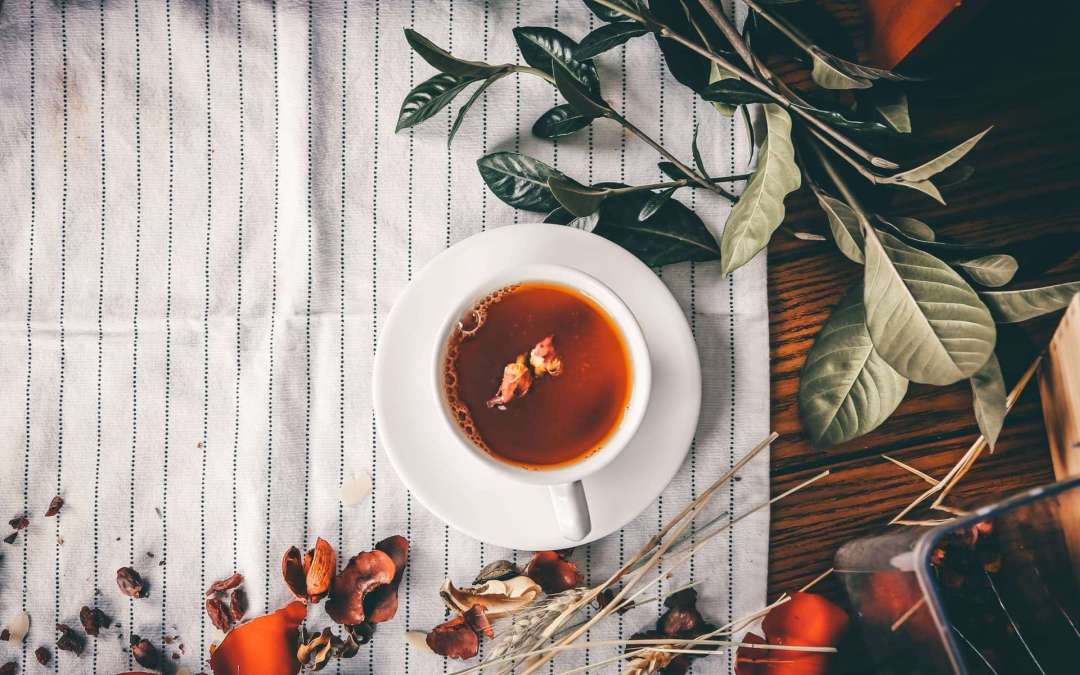 Tea (one of the best things for skin) with a flower floating in it on a saucer on a table with tablecloth and a plant nearby