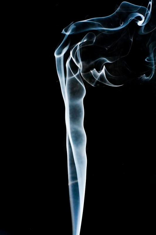 Smoke rising in front of blank background, such as one would see when smoking tea.