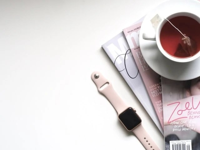 Tea cup on a pile of books next to an Apple watch