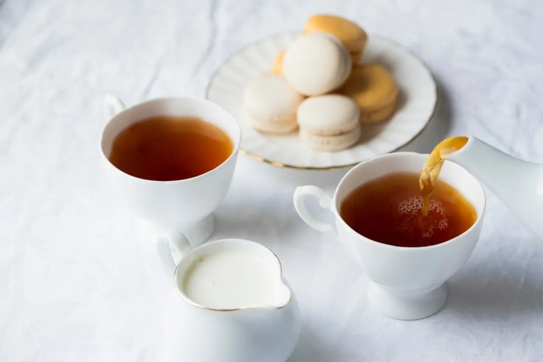 2 teacups, a dish of macarons, and a dish full of cream