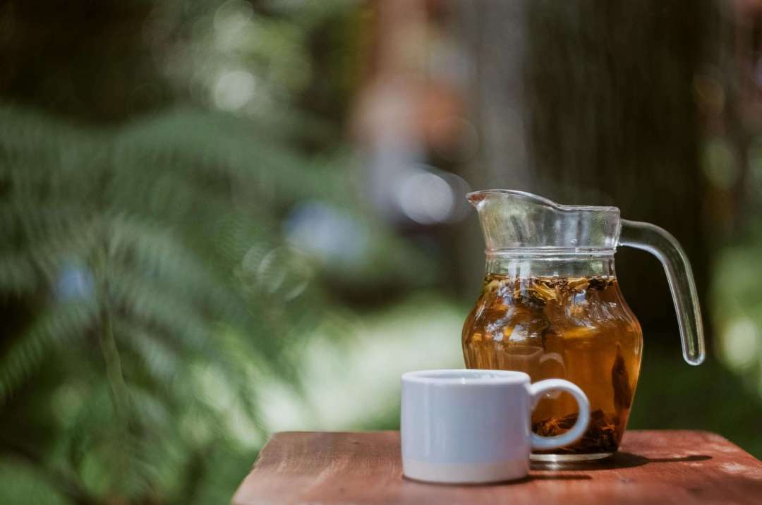 Clear glass pitcher of cold-brew tea on a table next to a cup
