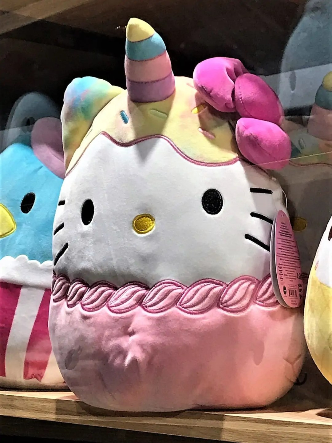 A Squishmallow stuffed toy with Hello Kitty's face, sprinkles, and a unicorn horn