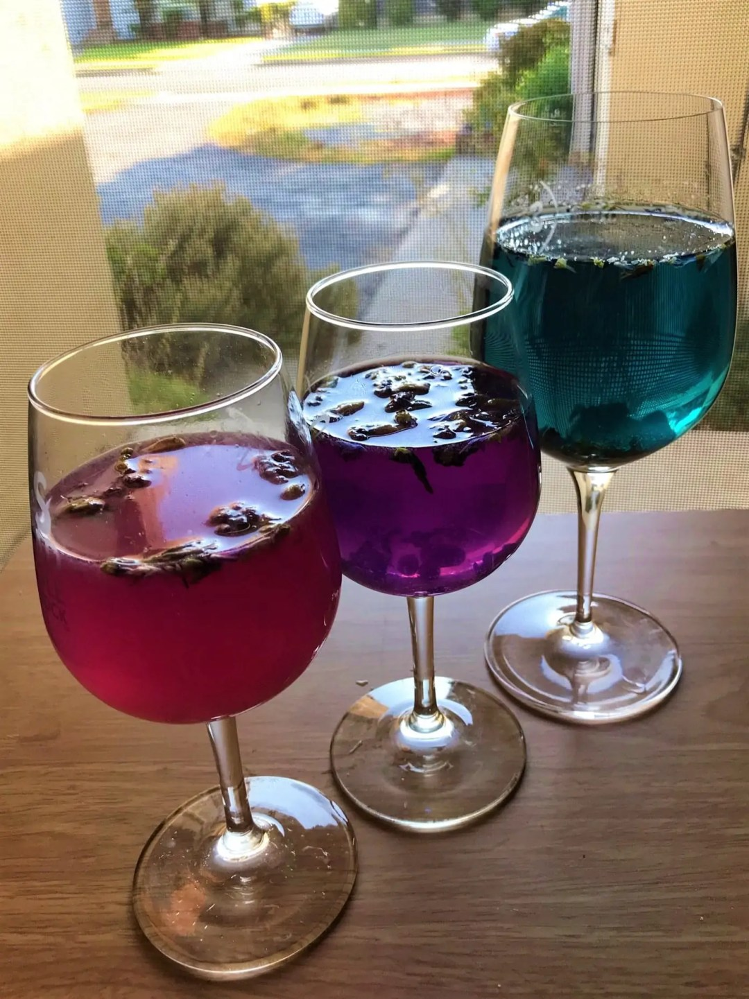 Three wine glasses with unicorn tears tea, each in a different color, in a row