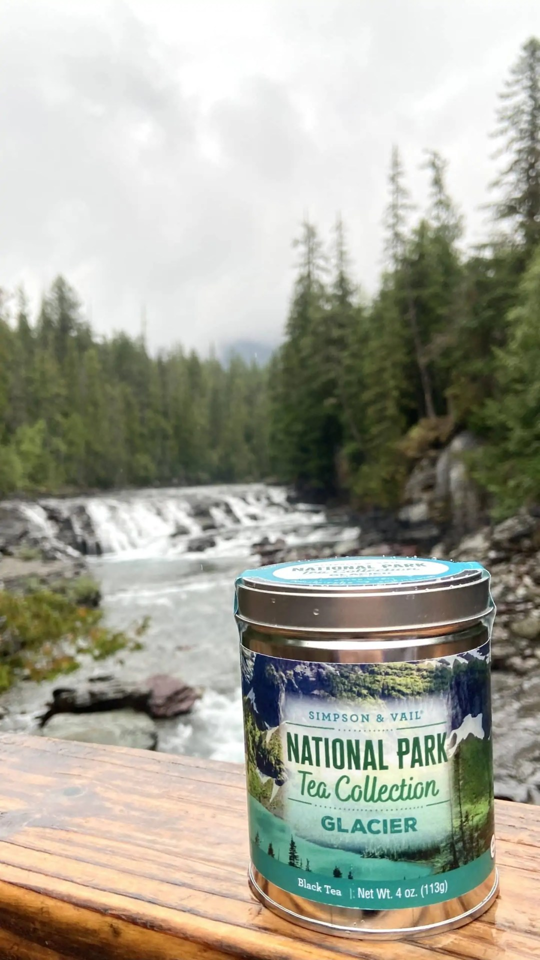 Tin of Glacier Tea in front of a river in a forest