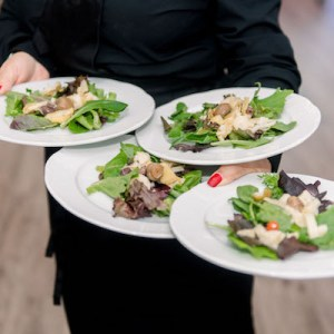 caterer holds plates of food