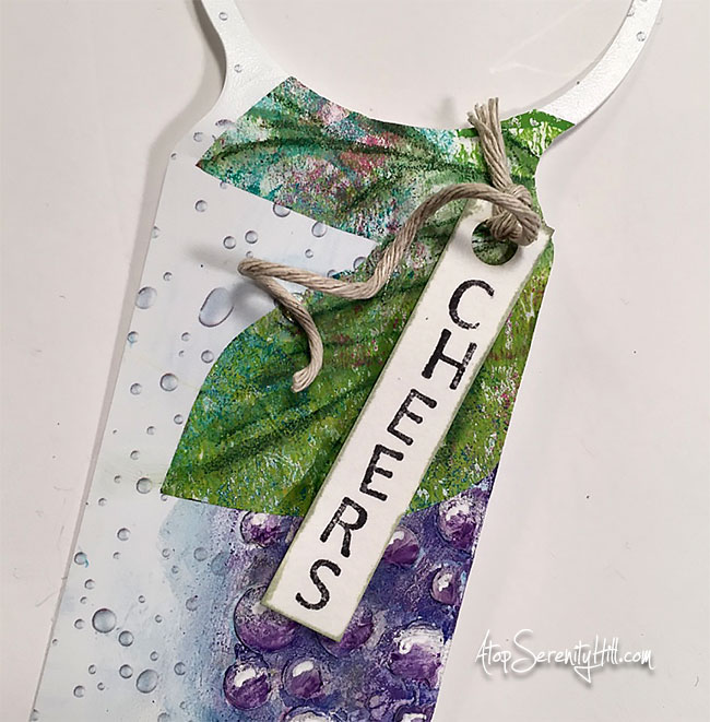 Wine bottle gift tag using a recycled product tag and a stencil from The Crafter's Workshop • AtopSerenityHill.com #gifttag #wine #stencil