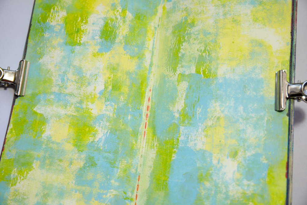 Paint page randomly with yellow, green and blue acrylic paint.