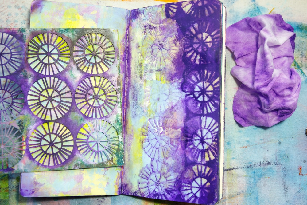 Spread deep colour over right hand portion of page and remove some of it through a stencil with a baby wipe.