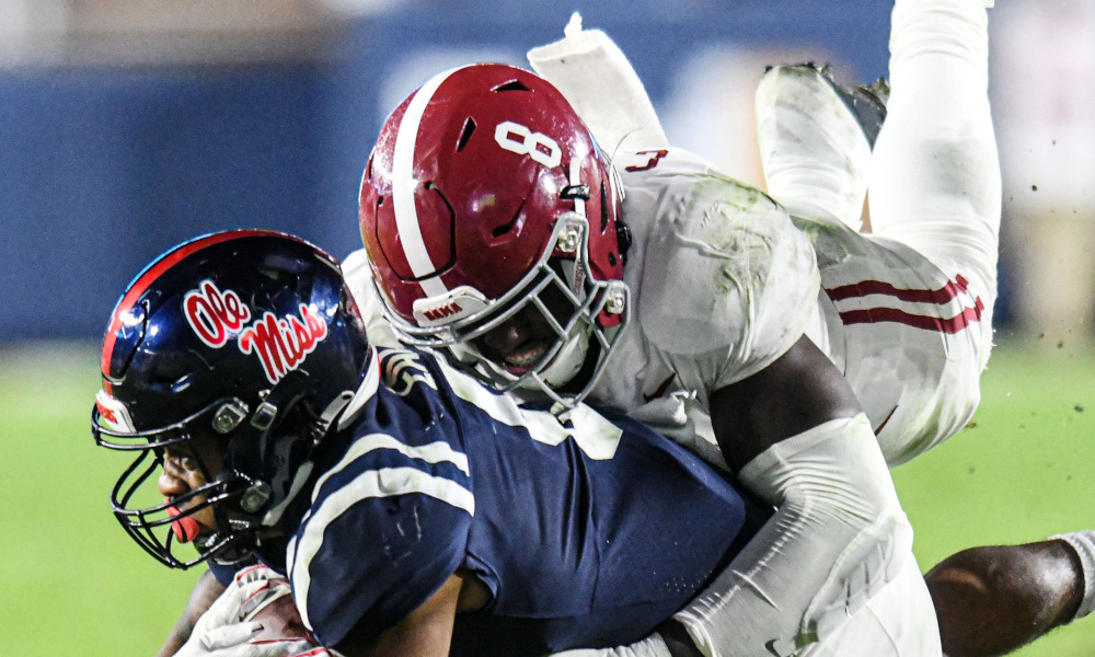 Christian Harris (No. 8) of Alabama tackles Jerrion Ealy of Ole Miss