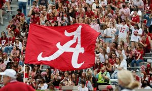 A flag is waved across the stands at Bryant-Denny Stadium