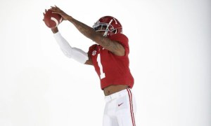 Jameson Williams holds ball in catch position for Alabama in photoshoot