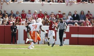Bryce Young throws a pass on the run against Mercer