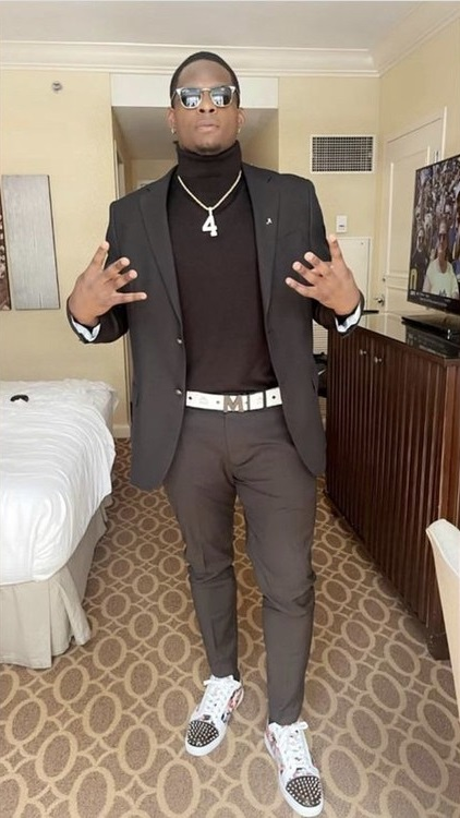 Brian Robinson throwing up the number four posing with his pregame outfit
