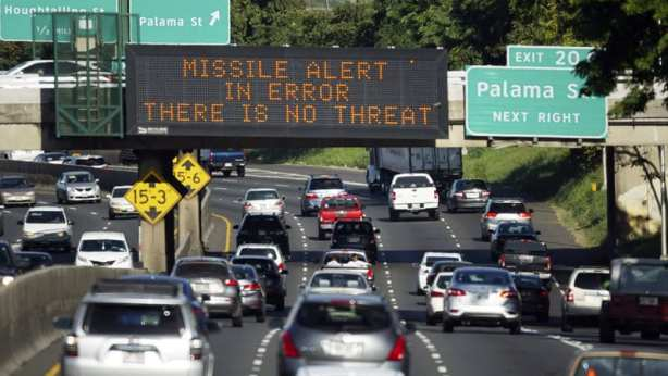 """Four lanes of traffic (approximately 30 cars) with large electronic sign shown """"Missile alert in error. There is no threat"""". On the right is a standard highway sign """"Exit 20 C - Palama St"""""""